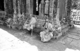 Cambodia, monks resting among Bayon Temple ruins at Angkor Thom