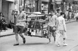 Hong Kong, laborers carrying luggage with yoke through city street