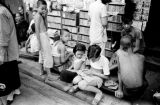 Hong Kong, children gathered in front of stand with reading material