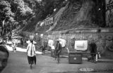 Hong Kong, pedestrians and sedan chairs near Peak Tram in Victoria