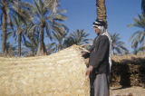 Basra (Iraq), man displaying woven straw mat