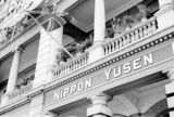 Hong Kong, British flag flying above sign for Nippon Yussen Kaisya shipping line