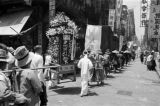 Hong Kong, men carrying shrine in procession through city street