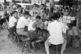 Cambodia, men eating at food stand on Phnom Penh sidewalk