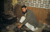 Baghdad (Iraq), seated man tending a fire