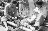 China, men working on deck of junk docked in Shanghai