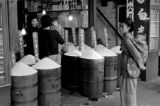 Hong Kong, woman with baby standing by barrels of grain displayed at shop