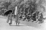 Cambodia, monks walking along path at Angkor Thom South Gate