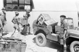 Hong Kong, Royal Army Service Corps soldiers loading jeep with supply crates