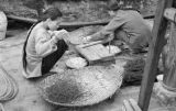 Hong Kong, women working with objects in baskets
