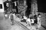 Hong Kong, children reading outside shop at Shek Kip Mei Estate public housing complex
