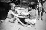 Hong Kong, boy and girl counting bottle caps in alley