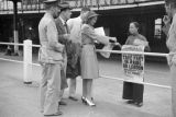 Hong Kong, American evacuees purchasing newspaper from vendor outside Hong Kong Ferry