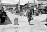 Hong Kong, woman walking through Shau Tau Kok village past border marker