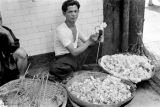 Hong Kong, man making decoration using flowers from baskets