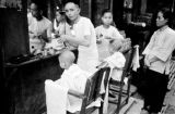 Hong Kong, woman watching barber cut boy's hair