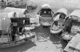 Hong Kong, women on small wooden boats tied together at dock