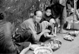 Hong Kong, women with bowls of food sitting on city sidewalk