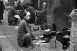 Hong Kong, woman cooking on small stove on city sidewalk