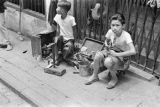 Hong Kong, boys providing shoe repair services on city sidewalk
