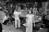 Hong Kong, girl standing in front of fruit stand