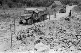 Vietnam, military trucks making way through bombed road during First Indochina War