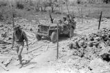 Vietnam, soldiers and military truck on bombed road during First Indochina War