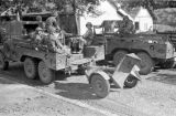 Vietnam, soldiers riding in trucks towing equipment during First Indochina War