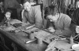 China, man watching boy use hand tools at workshop in Shanghai