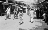 Pakistan, pedestrians and men on bicycles at Peshāwar market