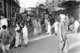 Pakistan, crowded market and carousel in Peshāwar