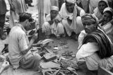 Pakistan, spectators watching shoe maker at Peshāwar market
