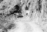 Philippines, men assisting car on mountain highway at northern Luzon island