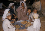 Iraq, group of men and children sitting together and eating