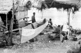 Indonesia, men constructing canoe on Sumbawa Island shore
