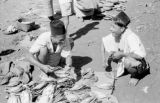 Indonesia, men selling dried fish at market on Sumbawa Island