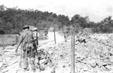 Vietnam, French troopers walking through bomb crater during First Indochina War