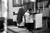 Indonesia, clergyman and altar boys at altar during morning mass in Ruteng