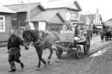 Japan, man leading horse-drawn cart down street