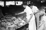 Indonesia, men purchasing dried fish from vendor at Banjarmasin market