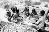 Indonesia, women in Martapura sifting sediment from dugout log