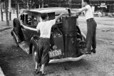 Japan, men feeding retrofitted taxi with charcoal in Tokyo