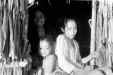 Indonesia, women and child at door of grass hut on Sumbawa Island