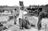 Indonesia, girl carrying water can for miners at Martapura diamond mine field