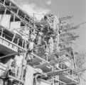 India, construction workers moving materials up on scaffolding in Ahmadabad