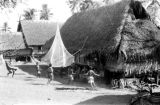 Indonesia, children playing outside thatched roof house in Mataloko
