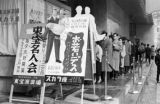 Japan, movie advertisement and line of people in front of Tokyo movie theater