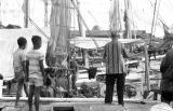Indonesia, Harrison Forman on Makassar dock looking at boats