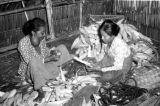 Indonesia, women husking corn inside home on Sumbawa Island