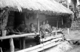Indonesia, villagers on porch of home in Mataloko